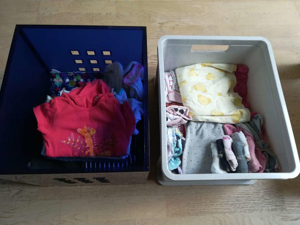 Zwei Kisten mit Kleidung für ein einjähriges Kind. Die linke Kiste enthält die aktuelle Kleidung, die rechte größere Größen, die das Kind tragen wird, wenn es älter ist. Die Datei ist eine Fotografie von Marion Schwenne im jpg-Format.