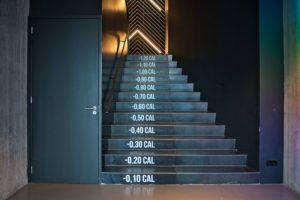 Treppenstufen mit Kalorienangaben in einem Fitnessstudio als Sinnbild dafür, dass Kalorienzählen Fressattacken auslöst. Das Foto im jpg-Format ist von Marcel Painchaud, veröffentlicht auf Unsplash.com.