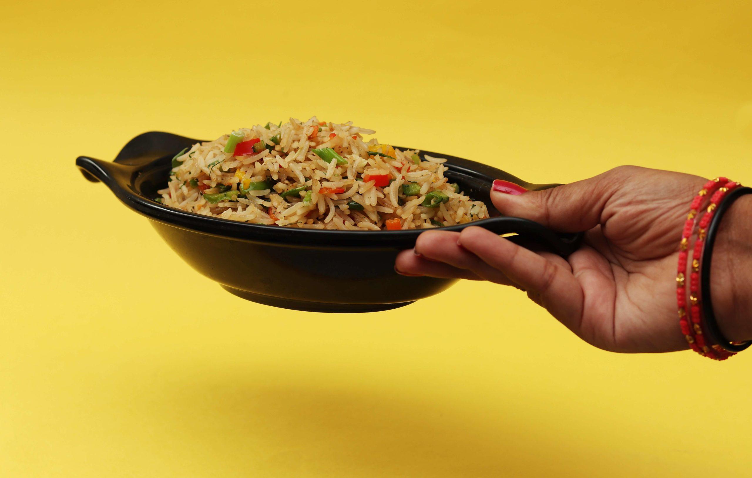 Mit der Umstellung auf vegane Ernährung kannst du Geld und Zeit sparen, wenn du dich auf Grundnahrungsmittel sowie saisonales und regionales Obst und Gemüse fokussierst. Das Bild zeigt eine Schüssel mit Reis und Gemüse. Veröffentlicht von Pixzolo Photography auf Unsplash.