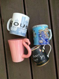 Vier verschiedene Tassen: Weihnachtstasse, Flamingotasse und zwei Andenken-Tassen.