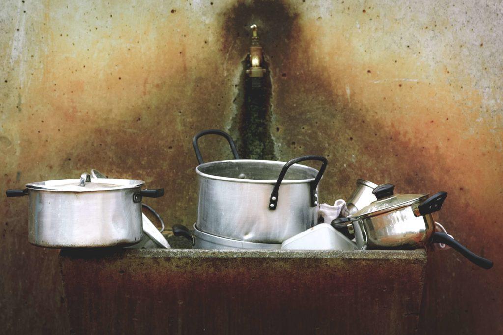 Schmutzige Töpfe stapeln sich im Waschbecken