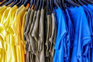 Die Fotografie zeigt gelbe, braune und blaue Basic-T-Shirts auf einem Ständer in Großaufnahme. Metapher für die Wegwerfmode der Fast Fashion Industrie. Fotografie im jpf-Format von analogicus, veröffentlicht auf Pixabay.